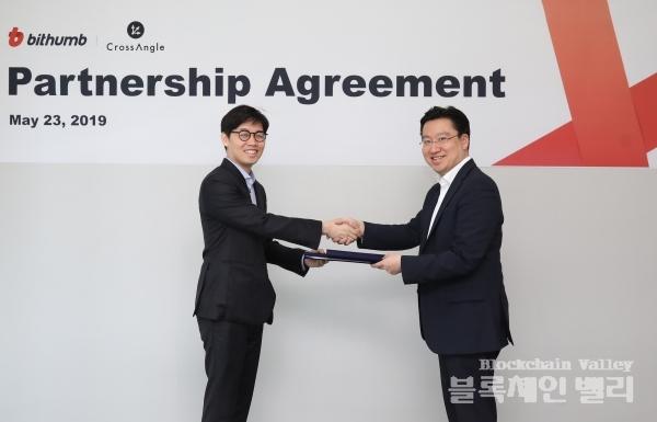 최재원 빗썸 대표(오른쪽)와 김준우 크로스앵글 대표가 지난 23일 서울 강남구 빗썸 본사에서 파트너십 협약을 맺고 악수를 하고 있다. /사진=빗썸